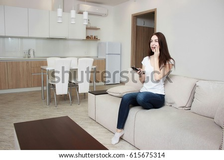 Beautiful young woman watching television sitting surrounded by cushions on a comfortable sofa with the remote control in her hand. #615675314