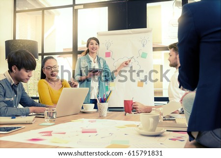 Asian young woman business officer explaining idea internal meeting to her project team in modern office. They are the multi ethnic business person group in casual suit. Project and Business concept. #615791831