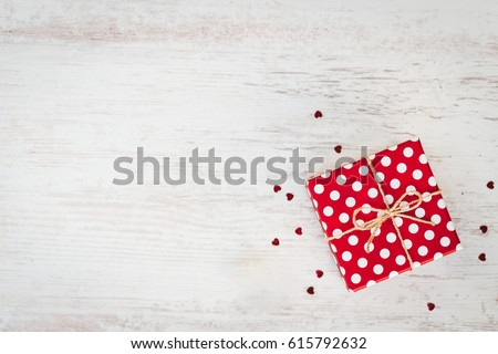 Top view of a red dotted gift box over white wood background. Copy space.