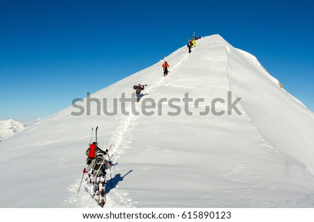 Group of free riders climbing a mountain peak nearby ski resort area in the French Alps, in a clear winter day. #615890123