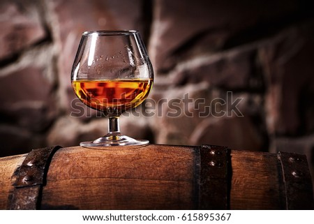 Glass of cognac on the old wooden barrel Royalty-Free Stock Photo #615895367