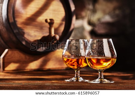 Two glass of Cognac and old oak barrel defocussed Royalty-Free Stock Photo #615896057