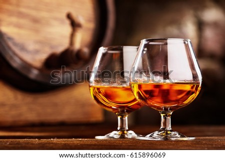 Two glass of Cognac and old oak barrel defocussed Royalty-Free Stock Photo #615896069