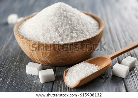 Bowl and scoop with white sand and lump sugar on wooden background #615908132