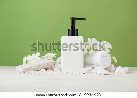 SPA Decoration. Spa composition with cosmetic bottle over green.