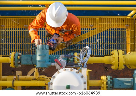 Offshore oil rig worker calibrating coriolis digital flow meter by using hand held communicator to connect between devices, instrument and electrical service of oil and gas energy business. Royalty-Free Stock Photo #616064939