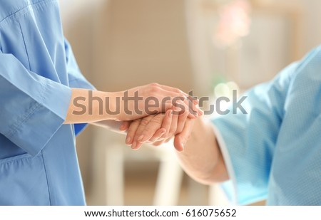Young doctor holding hand of elderly woman on light background, closeup Royalty-Free Stock Photo #616075652