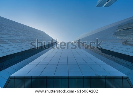 Infinite Corporate Buildings. Business offices skyscrapers on blue sky background. Low angle view of tall corporate buildings. #616084202
