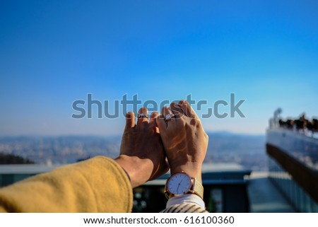two hands with beautiful wedding rings on sky background.(Selective focus) #616100360