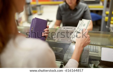 shopping, payment, consumerism and people concept - woman paying money and cashier at store cash register #616164857