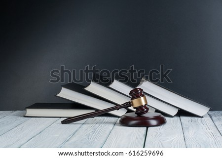 Law concept - Open law book with a wooden judges gavel on table in a courtroom or law enforcement office on blue background. Copy space for text #616259696