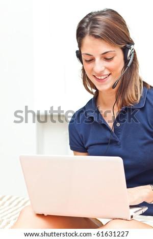 Beautiful girl using her laptot wearing headphones to communicate #61631227