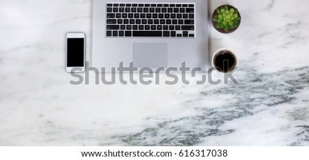 Flat lay of a partial laptop, plant, smartphone and dark coffee on natural marble desktop #616317038