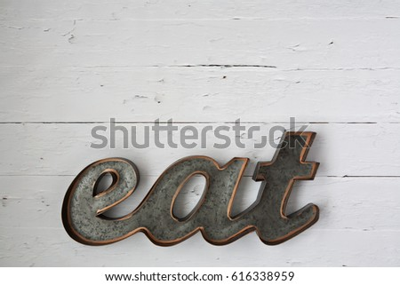 Rustic, metal 'eat' sign on a white wooden backdrop. With space for copy. Horizontal flat lay.