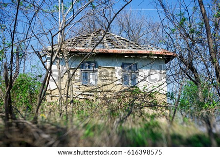 old abandoned rural house covered with grass #616398575