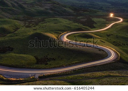 Winding curvy rural road with light trail from headlights leading through British countryside. #616405244