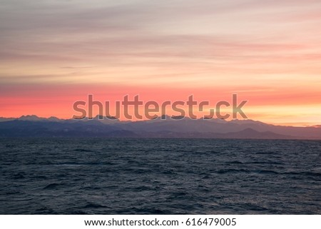 Beauty sunrise at sea. Snowy mountains at horizon and orange sky clouds. Caucasus. Abstract seascape background. #616479005