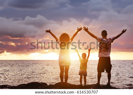 Happy family of father, mother and young son having fun at sunset beach. They greetings sea and sun #616530707
