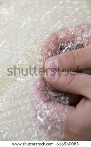 Popping the bubbles in bubble wrap - white background #616560083