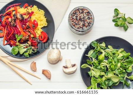 Healthy vegetarian diet concept. Rice and steamed vegetables, lamb's lettuce feldsalat on a black plates, c�hopsticks, napkin, garlic, mushrooms, raw multicolor rice in glass jar. White wooden table. #616661135