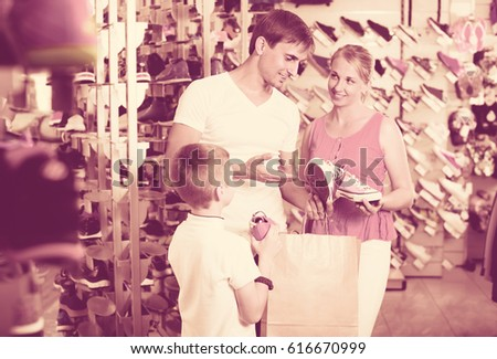 smiling young couple with schoolboy son choosing new sport shoes in sport shop. Focus on man
