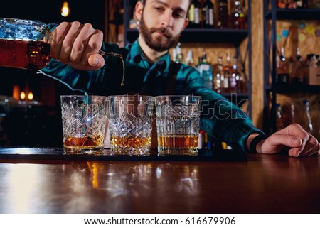 The barman pours alcohol into a glass. Close-up. #616679906
