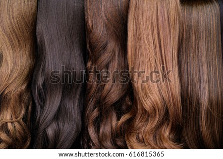 Close up brown and another color of hair wigs display in beauty salon. Royalty-Free Stock Photo #616815365