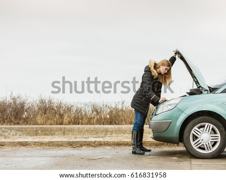 Accident and breakdowns with auto concept. Blonde woman and broken down car on road checking problem in engine #616831958