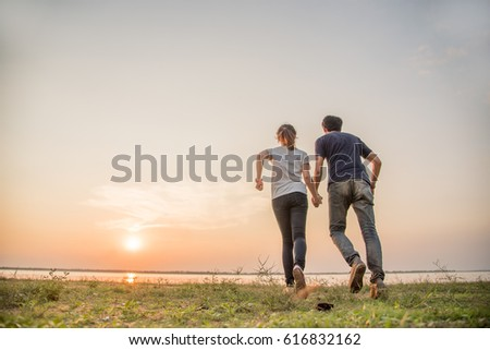 couple in love run at sea during sunset time #616832162