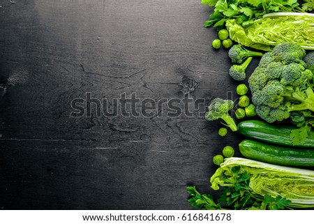 Collection of fresh green vegetables placed on black stone #616841678