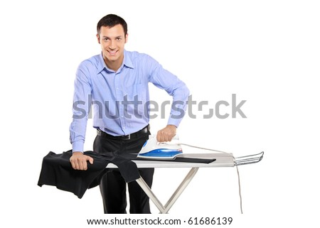 Happy young man ironing his clothes isolated on white background