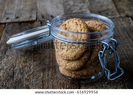 Milk and chocolate cookies on an old wooden table, black background #616929956