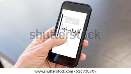 Digital composite of Businessman analyzing graphs on smart phone #616930709