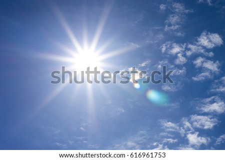 Bright direct sun with rays in a blue sky with clouds #616961753