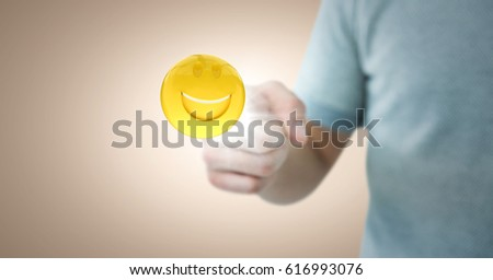 Digital composite of Man in tshirt pointing at emoji with flare against cream background #616993076