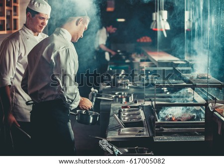 Food concept. Chef in white uniform monitors the degree of roasting and greases meat with oil in saucepan in interior of modern restaurant kitchen. Preparing traditional beef steak on barbecue oven. Royalty-Free Stock Photo #617005082