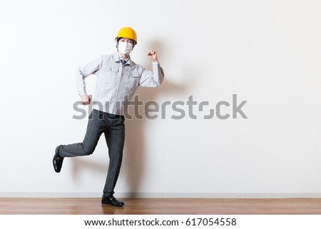 Men standing wearing work clothes with a white background #617054558