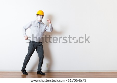 Men standing wearing work clothes with a white background #617054573