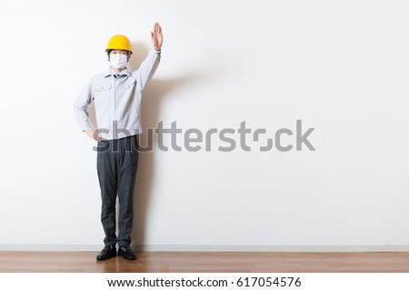 Men standing wearing work clothes with a white background #617054576