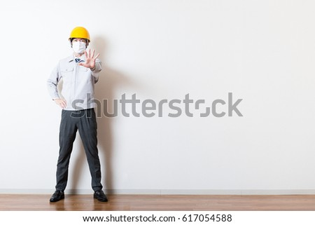 Men standing wearing work clothes with a white background #617054588