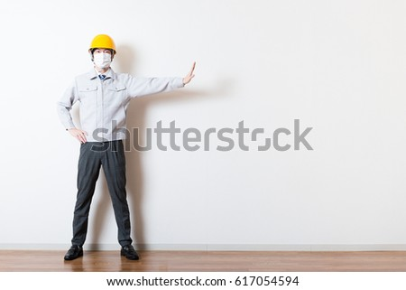 Men standing wearing work clothes with a white background #617054594