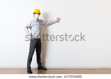 Men standing wearing work clothes with a white background #617054600