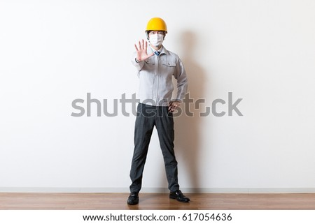 Men standing wearing work clothes with a white background #617054636