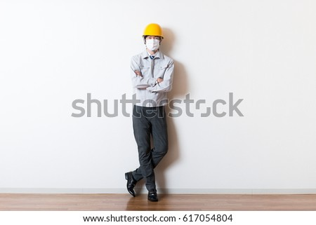 Men standing wearing work clothes with a white background #617054804