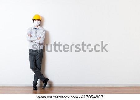 Men standing wearing work clothes with a white background #617054807