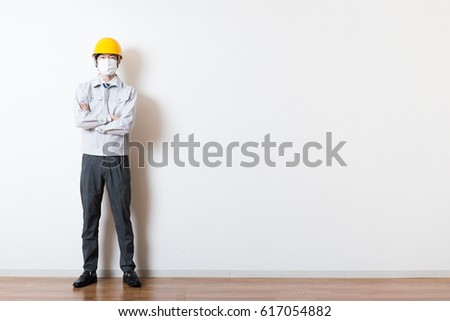 Men standing wearing work clothes with a white background #617054882