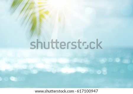 Blur beautiful nature green palm leaf on tropical beach with bokeh sun light wave abstract background. Copy space of summer vacation and business travel concept. Vintage tone filter effect color style