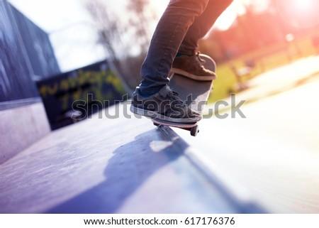 Skater boy doing five O trick on ramp coping in skatepark #617176376