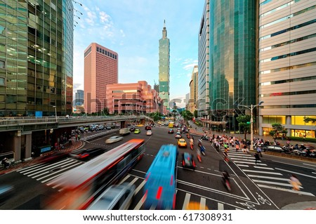 View of a busy street corner in Downtown Taipei City at rush hour with cars & buses dashing by, Taipei 101 Tower & World Trade Center Building in Xinyi Financial District & people passing on crosswalk #617308931