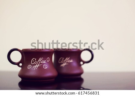 cup of coffee black background. Mug with coffee on a black table #617456831
